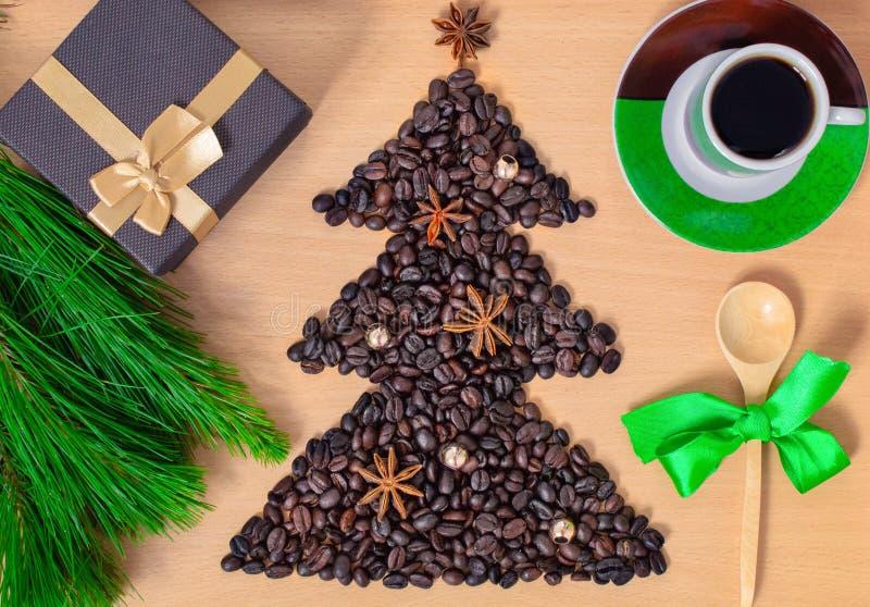 Kopp kaffe med julgåvor och garneringar Shape av julträdet som göras av kaffebönor på trätabellen arkivbild