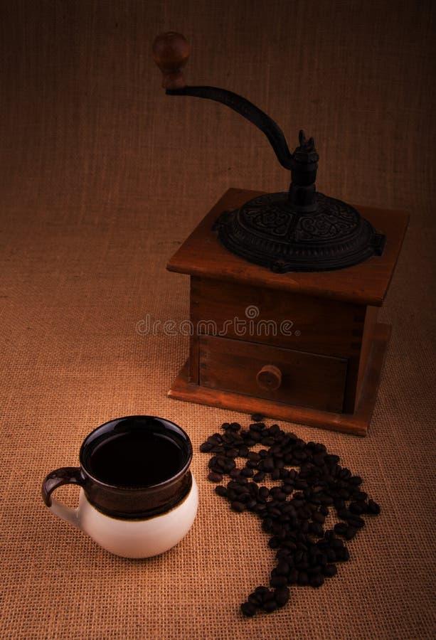 Kopp kaffe med kaffebönor och en gammal molar på bakgrund royaltyfri bild