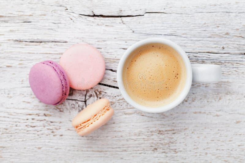 Kopp kaffe med macaron på den vita trätabellen från över, framlänges lekmanna- royaltyfria foton