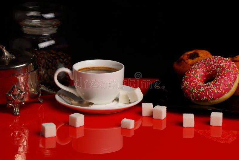 Kopp kaffe med munken och socker på en röd glansig tabell arkivbilder