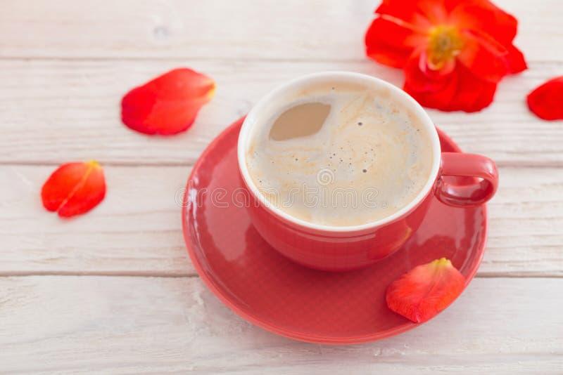 Kopp kaffe med röda blommor på den vita trätabellen arkivbild