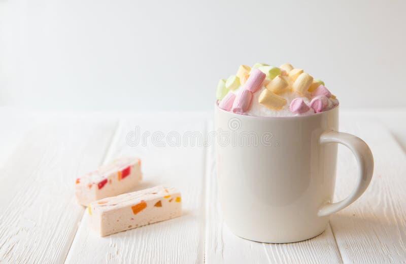 Kopp kaffe med s?t souffle med stora bitar och marshmallower p? en vit tabell royaltyfri foto