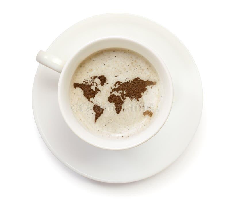 Kopp kaffe med skum och pulver i formen av världen (serie royaltyfri fotografi