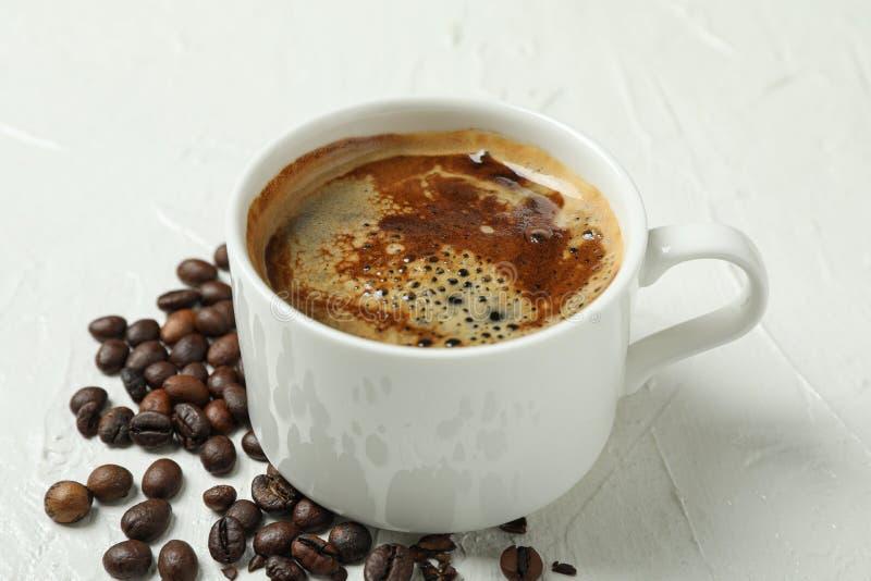 Kopp kaffe med skummiga skum- och kaffebönor på den vitt bakgrund, closeupen och utrymme för text fotografering för bildbyråer