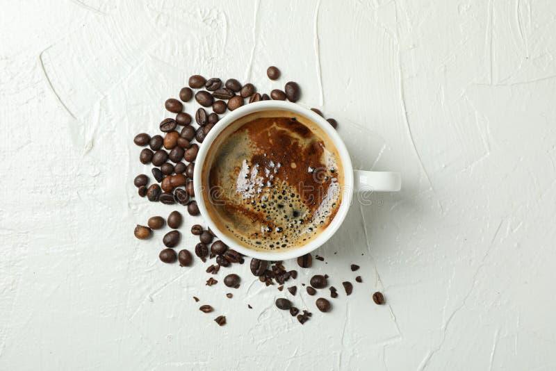 Kopp kaffe med skummiga skum- och kaffeb?nor p? vit bakgrund, b?sta sikt och utrymme f?r text royaltyfri fotografi