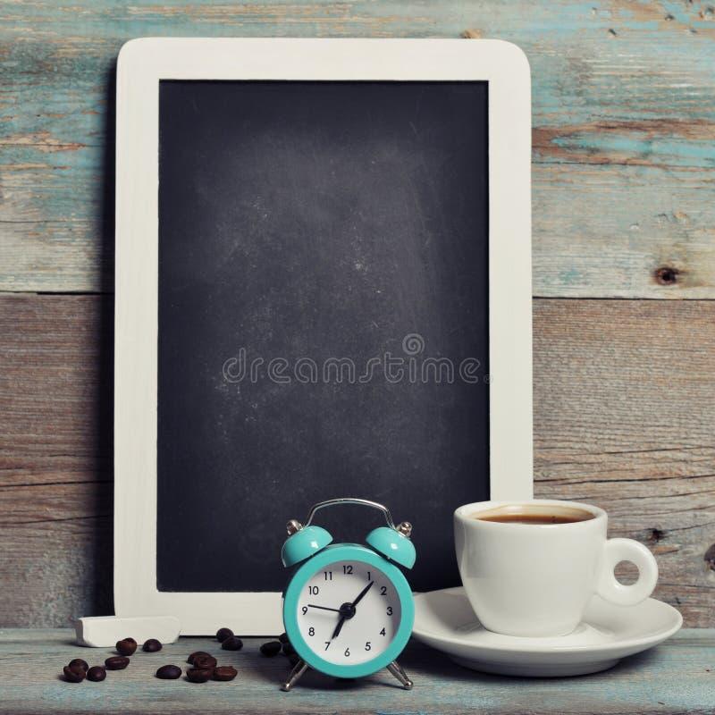 Kopp kaffe med svart tavla arkivbild