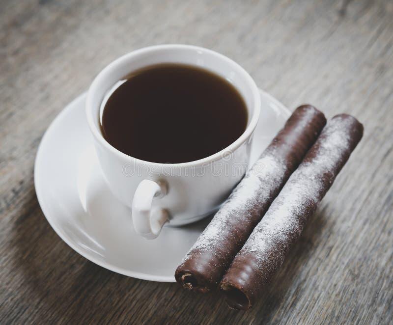 Kopp kaffe med två chokladrullar arkivbilder