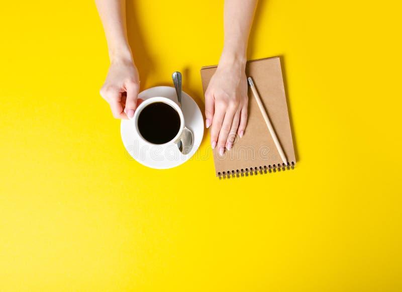 Kopp kaffe notepad, blyertspenna, kvinnliga händer royaltyfria foton