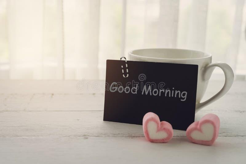 Kopp kaffe och hjärtaformgodis arkivbild