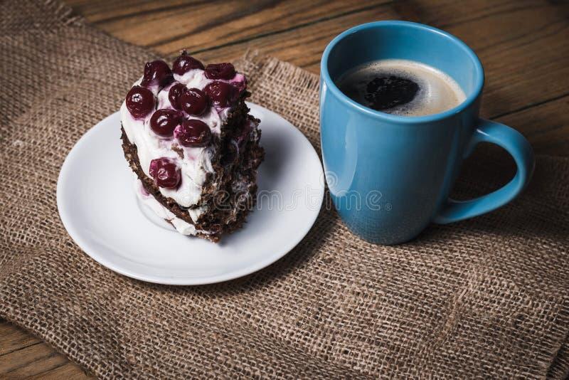 Kopp kaffe och körsbärsröd kaka fotografering för bildbyråer