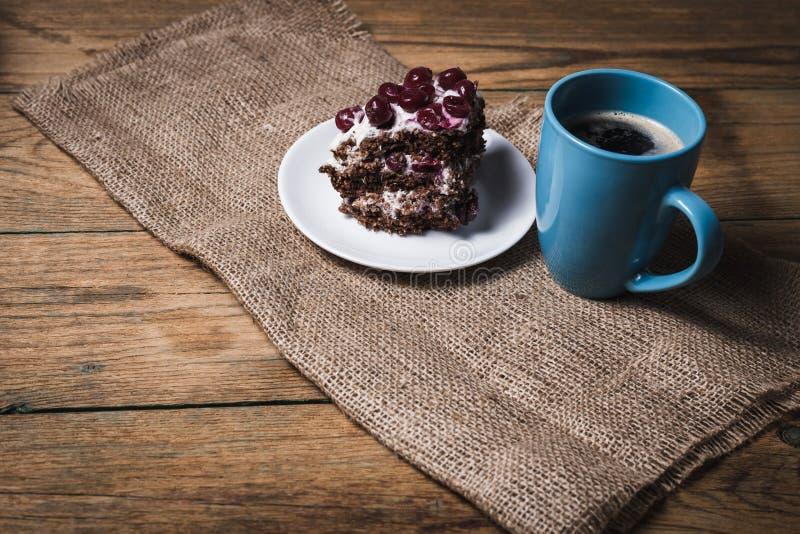 Kopp kaffe och körsbärsröd kaka royaltyfria foton