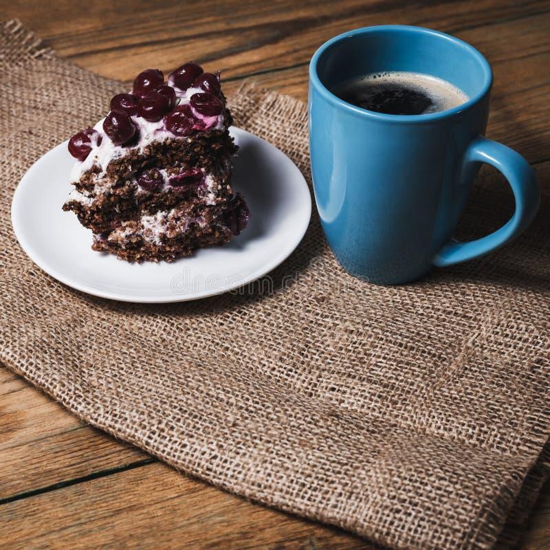 Kopp kaffe och körsbärsröd kaka royaltyfri foto
