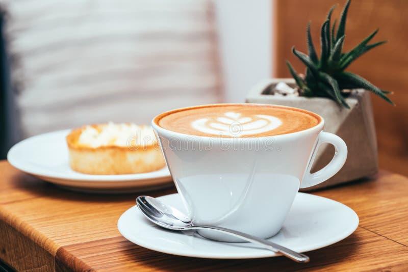 Kopp kaffe och kaka på en trätabell i ett kafé royaltyfria foton