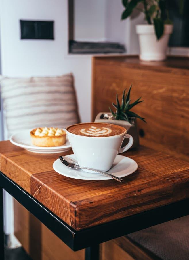 Kopp kaffe och kaka på en trätabell i ett kafé royaltyfri foto