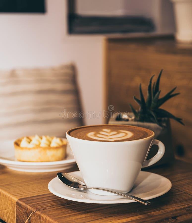 Kopp kaffe och kaka på en trätabell i ett kafé arkivbilder