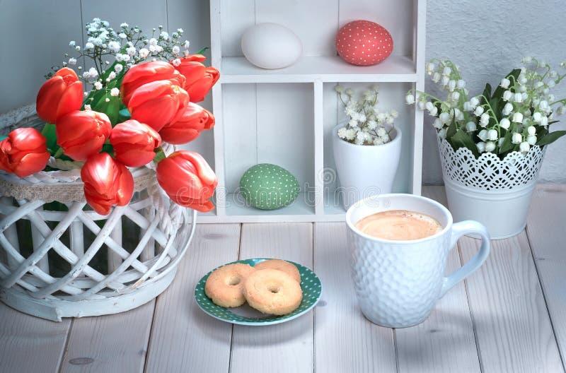 Kopp kaffe och kakor på den vita trätabellen med röda tulpan royaltyfri foto
