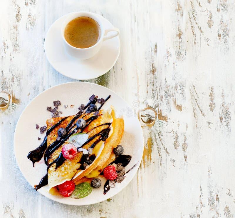 Kopp kaffe och kräppar med nya bär royaltyfri fotografi