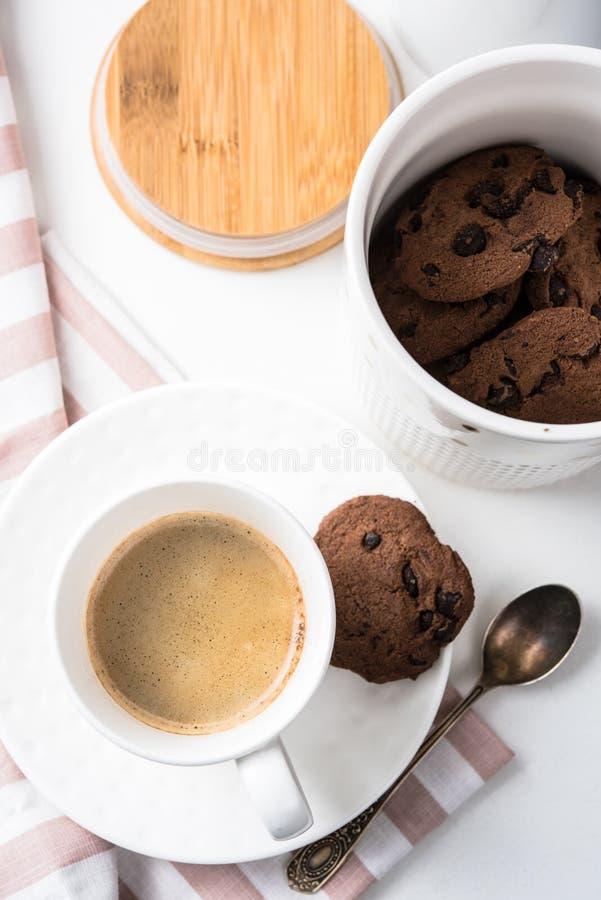 Kopp kaffe och krus av chokladkakor royaltyfri bild
