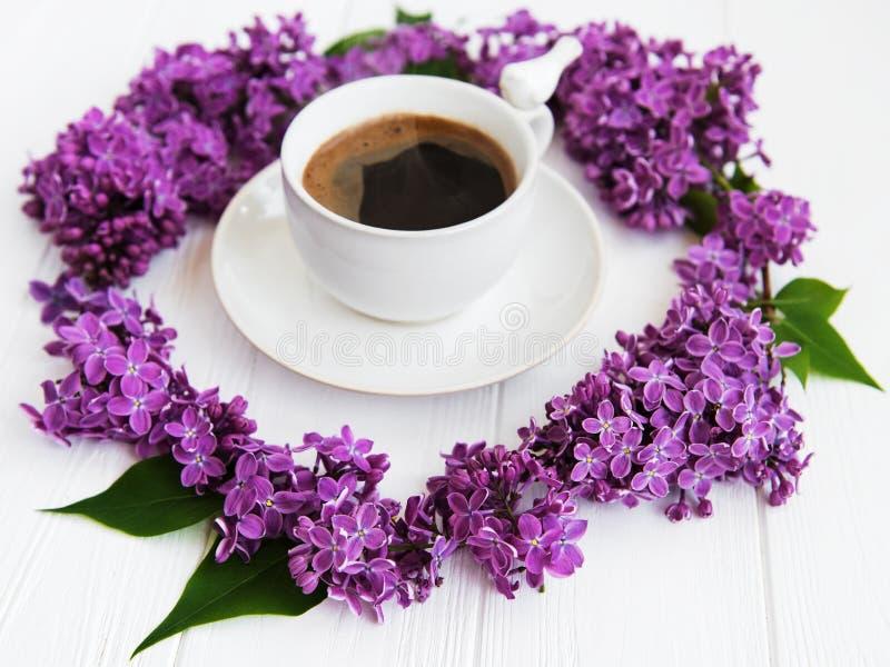 Kopp kaffe- och lilablommor royaltyfria bilder