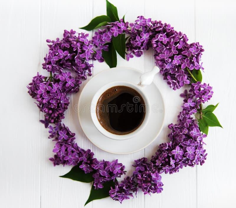 Kopp kaffe- och lilablommor arkivbild