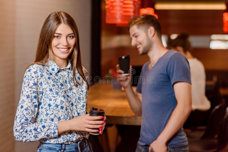 Kopp kaffe och man för ursnygg kvinna som hållande tar fotoet av henne arkivbild