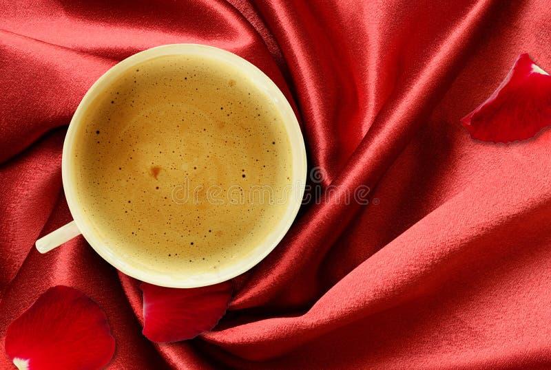 Kopp kaffe och rosa kronblad på vikt rött silke arkivbild
