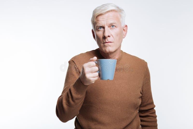 Kopp kaffe och rynka pannan för hög man hållande arkivfoto