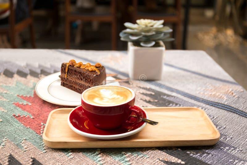 Kopp kaffe och stycke av macadamiachokladkakan royaltyfri foto