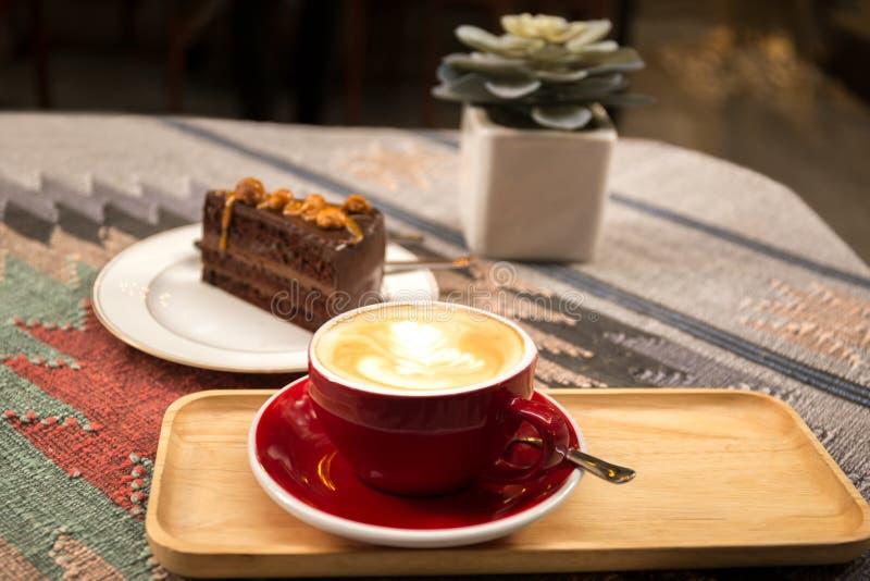Kopp kaffe och stycke av macadamiachokladkakan fotografering för bildbyråer