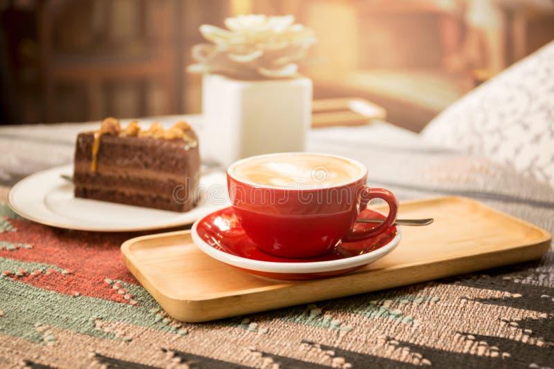 Kopp kaffe och stycke av macadamiachokladkakan arkivfoton