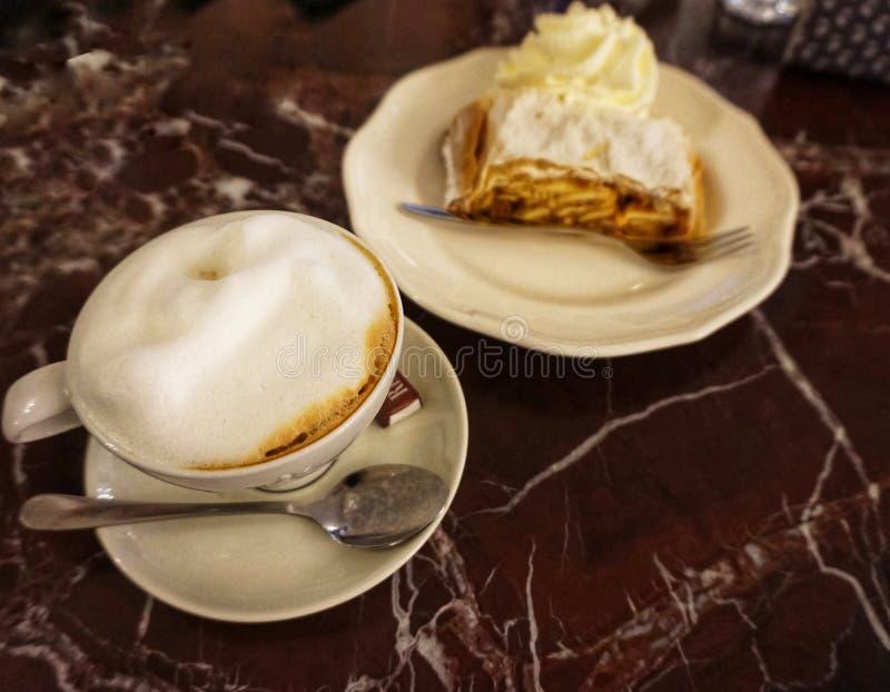 Kopp kaffe och wiensk äpplestrudel på en platta royaltyfri bild