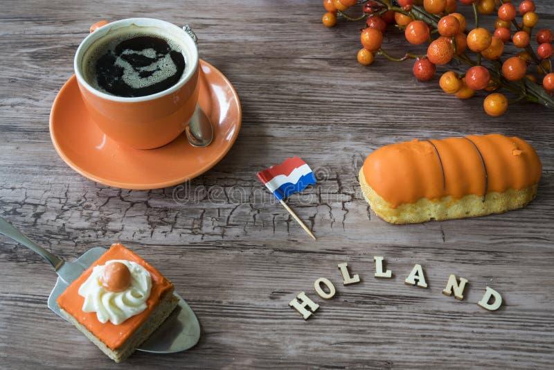 Kopp kaffe, orange kaka och eclaire f?r den typiska holl?ndska h?ndelsen Koningsdag, konungdag royaltyfri fotografi