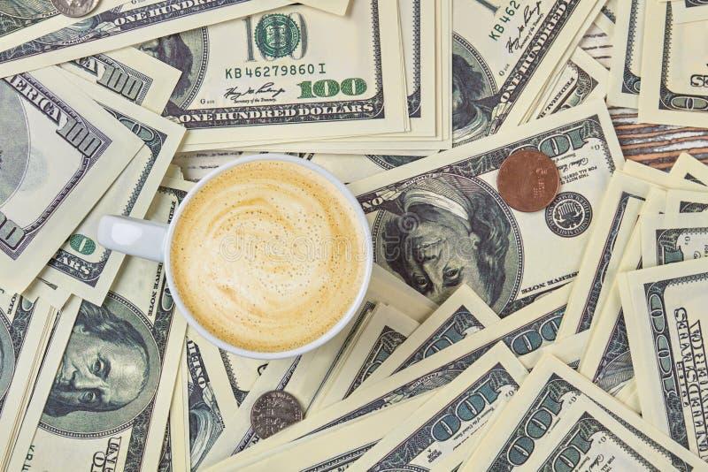 Kopp kaffe på en hög av pengar royaltyfri bild