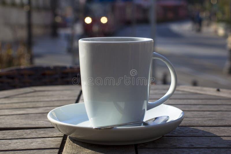 Kopp kaffe på en trätabell utomhus royaltyfri foto