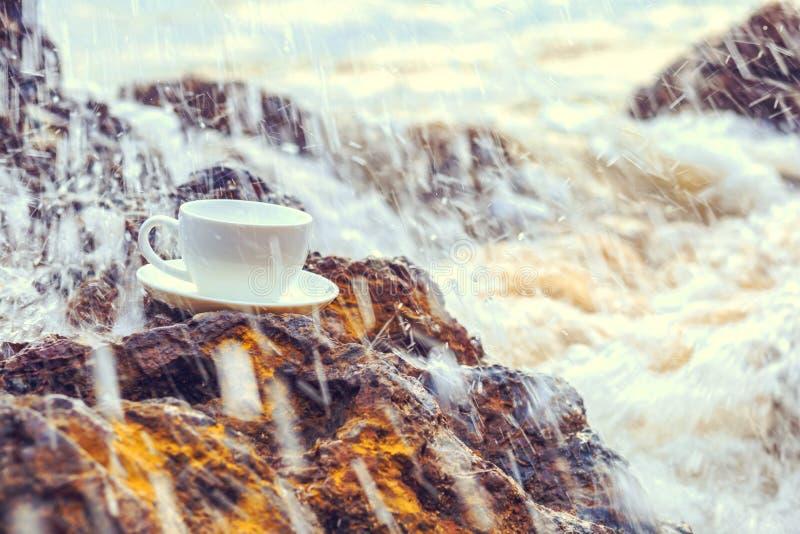 Kopp kaffe på stenen i strand- och vattenfärgstänket royaltyfri foto