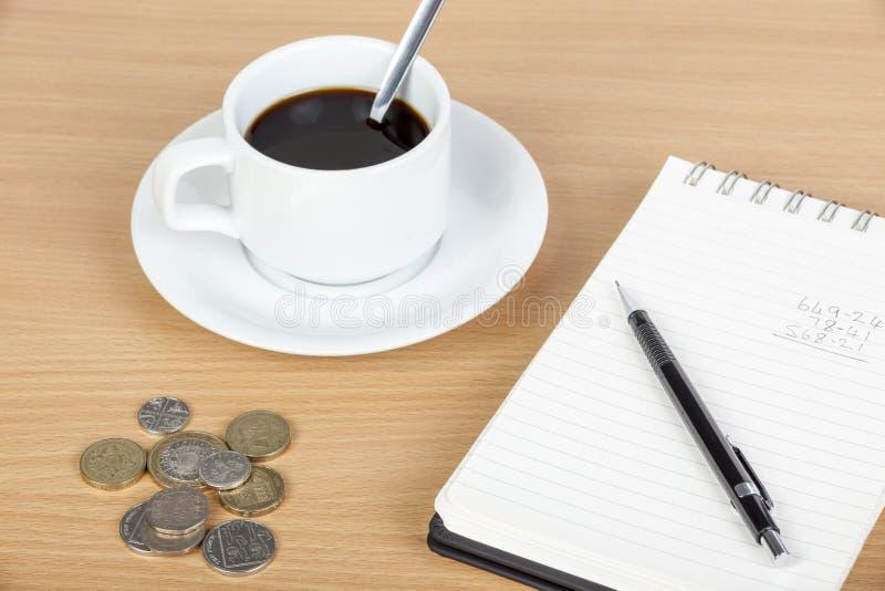 Kopp kaffe på tabellen med notepaden och coinage arkivbilder