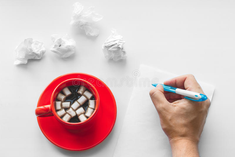 Kopp kaffe på tefatet med marshmallower, handen med pennhandstil på ett tomt ark av papper och skrynkliga ark av papper Affär fotografering för bildbyråer