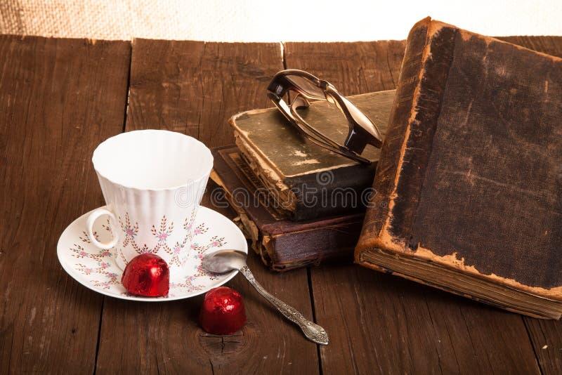 Kopp kaffe, shokolad, exponeringsglas och bunt av gamla böcker på nollan royaltyfria bilder