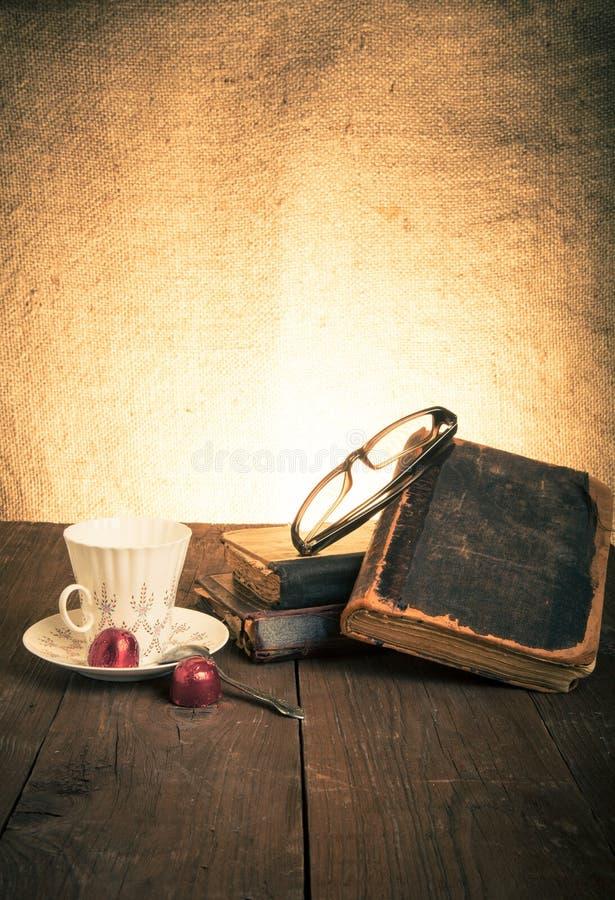 Kopp kaffe, shokolad, exponeringsglas och bunt av gamla böcker på nollan royaltyfri foto