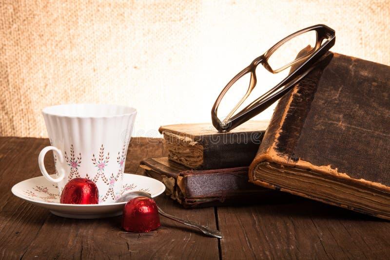 Kopp kaffe, shokolad, exponeringsglas och bunt av gamla böcker på nollan arkivfoto