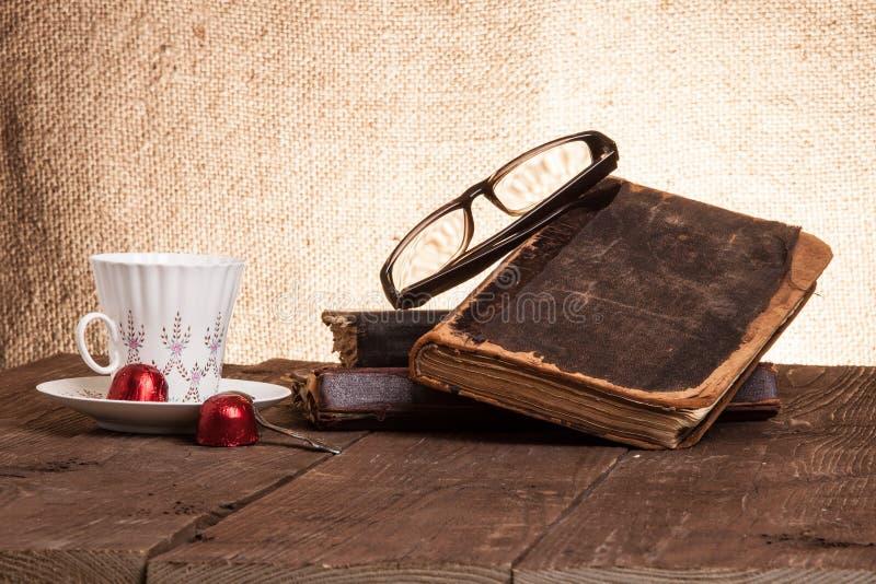 Kopp kaffe, shokolad, exponeringsglas och bunt av gamla böcker på nollan royaltyfria foton