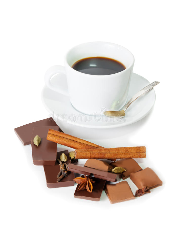 Kopp kaffe, stycken av choklad och kryddor som isoleras på vit royaltyfri bild