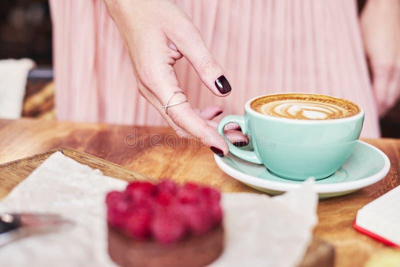 Kopp kaffelatte och söt bakelse på trätabellen i kvinnahänder Det försiktiga romantiska lynnet, bärande rosa färg för flicka krin royaltyfri bild