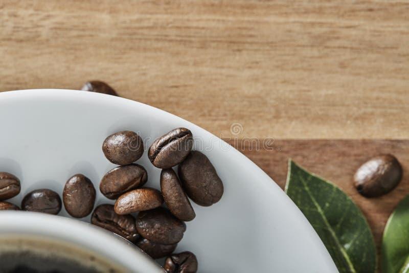 Kopp kaffewhitböna och gräsplanblad på trätabellen med kopieringsutrymme Top beskådar royaltyfria foton