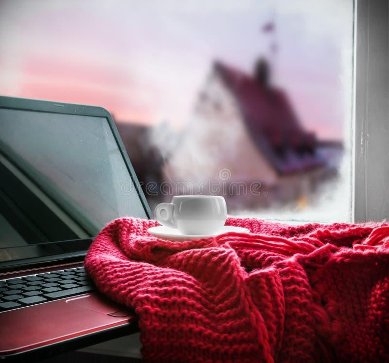 Kopp med en varm drink och bärbar dator för på fönsterbrädan arkivbilder