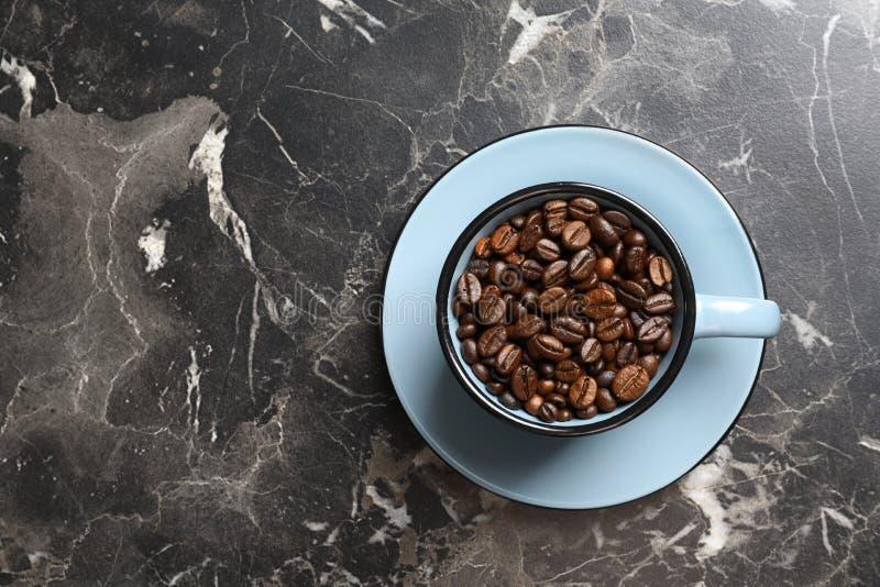 Kopp med grillade kaffebönor och utrymme för text på grå bakgrund arkivbilder