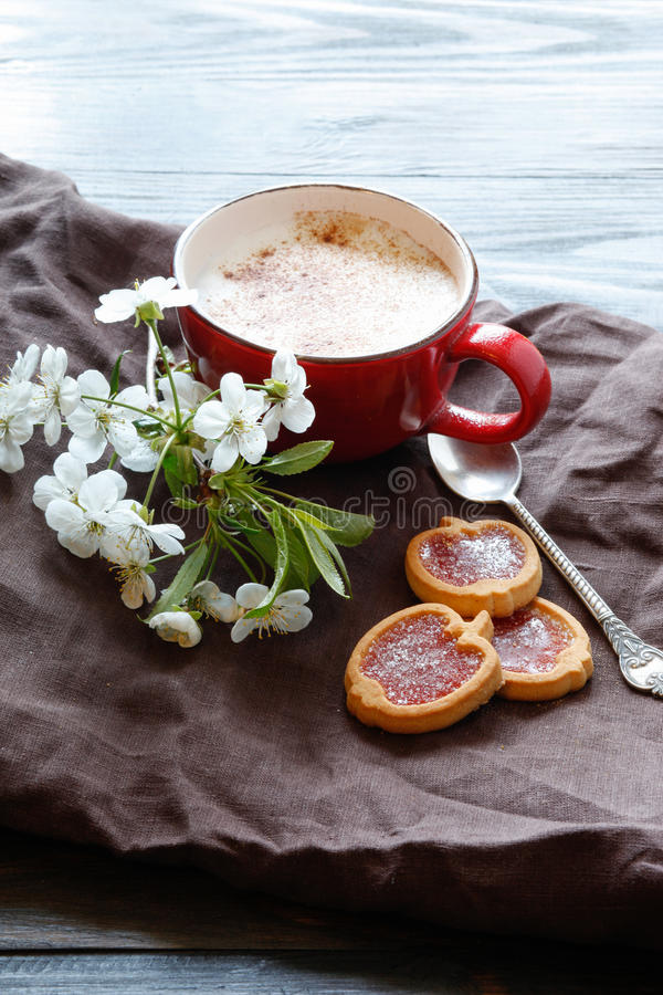 Kopp med kaffe och körsbärsröd blomning och kakor royaltyfri fotografi