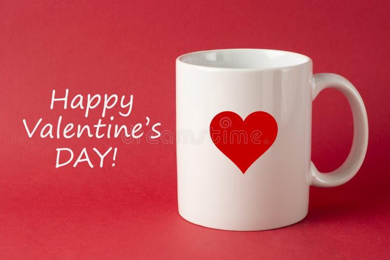 Kopp med lycklig Valentine' s-daginskrift, ord för valentindag på röd bakgrund Förälskelseberöm royaltyfri bild