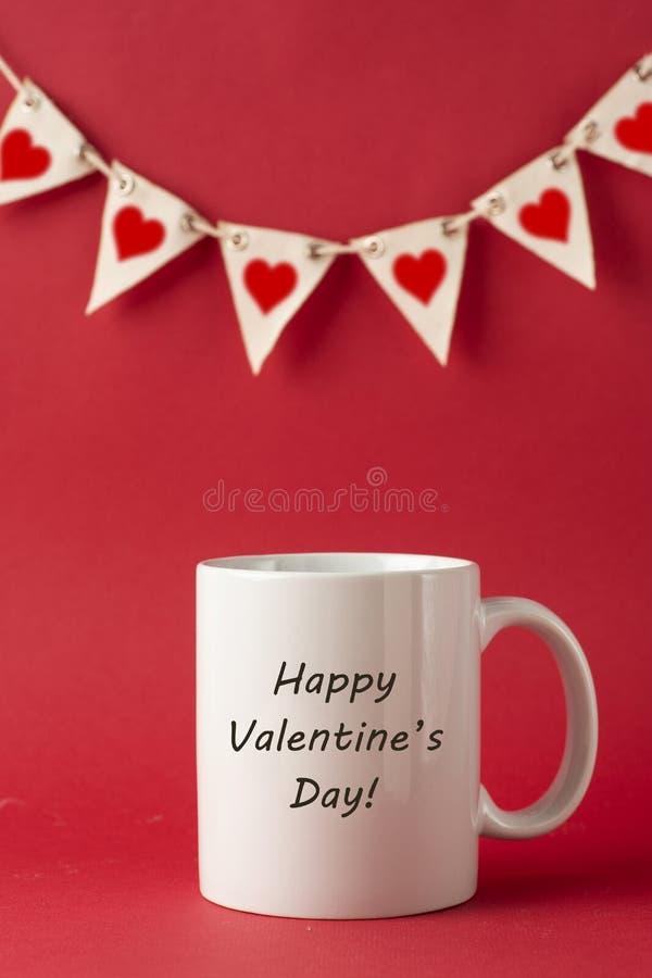 Kopp med lycklig Valentine' s-daginskrift, ord för valentindag på röd bakgrund Förälskelseberöm fotografering för bildbyråer