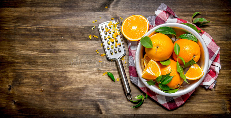 Kopp med nya apelsiner, piff och rivjärnet på tyg arkivbild